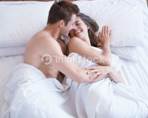 Couple on bed covered by white sheets by pleasure shop