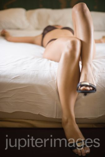 Girl lying on bed with black underwear by Pleasure Shop